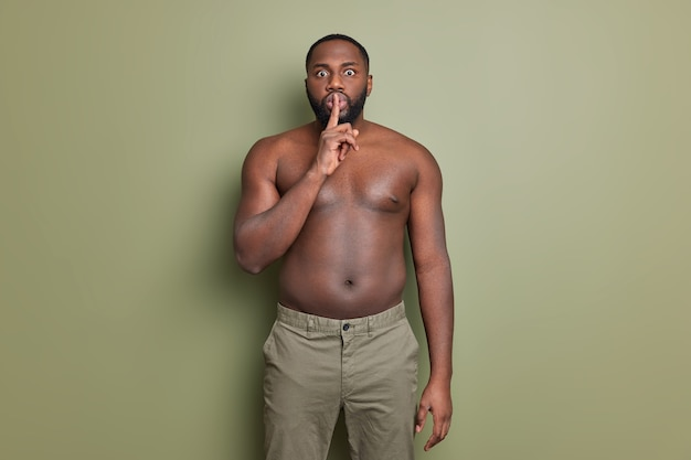 Das foto eines überraschten bärtigen mannes macht eine shush-geste, die besagt, dass die stille still ist und den zeigefinger über den lippen hält
