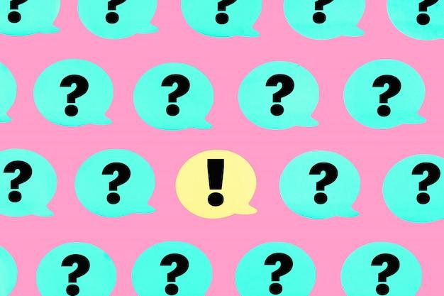 Das foto, türkisaufkleber mit fragezeichen auf rosa mit einem ausrufezeichen.