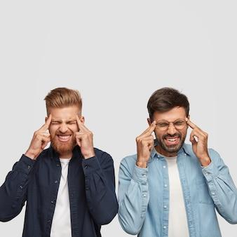 Das foto von zwei unzufriedenen männern erinnert sich an wichtige details