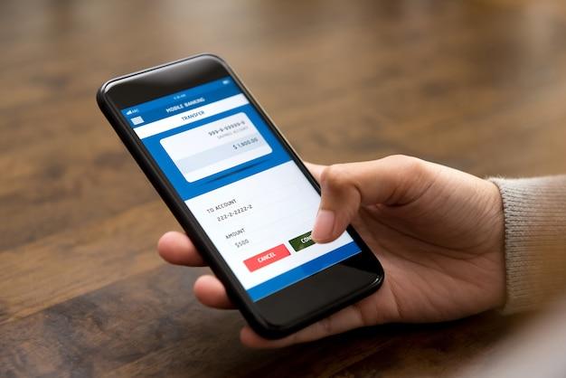 Das frauenhandberühren bestätigt knopf auf dem smartphoneschirm und überträgt geld online