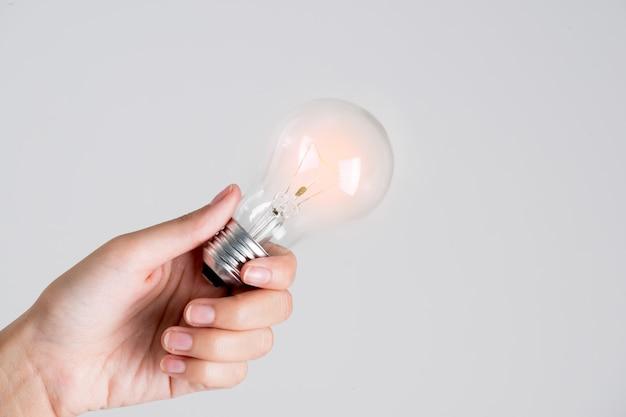 Das frauenhandgeben schalten eine glühlampe auf weißem hintergrund ein