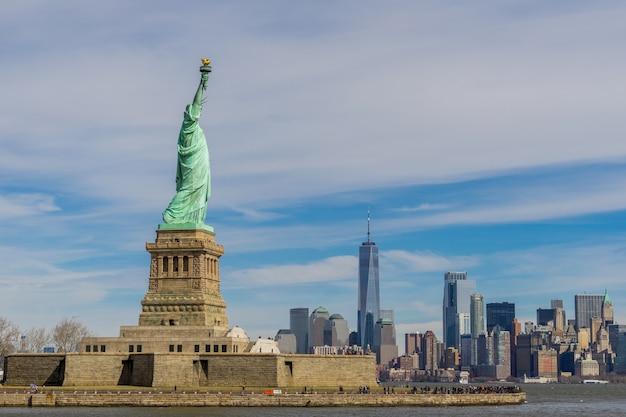 Das freiheitsstatue auf freiheitsinsel mit new york city manhattan im stadtzentrum gelegen