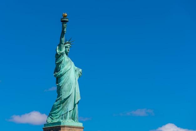 Das freiheitsstatue unter der wand des blauen himmels, dem lower manhattan, new york city, der architektur und dem gebäude