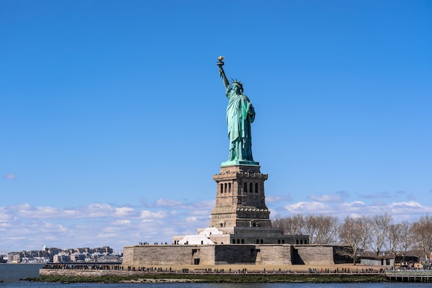 Das freiheitsstatue unter der wand des blauen himmels, lower manhattan, new york city