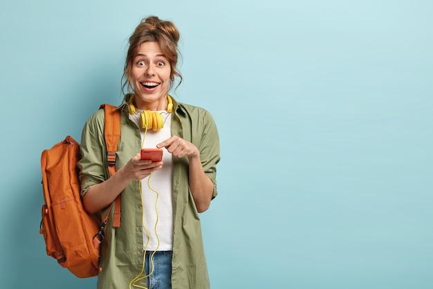 Das freudige hipster-mädchen freut sich darauf, mit freunden zu plaudern, sieht sich ein lustiges video auf einem neuen gerät an, zeigt auf den bildschirm und hat kopfhörer am hals