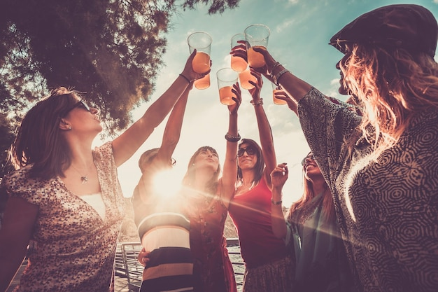 Das freundschafts- oder erfolgsteam feiert im freien mit farbigem saft und 7 schönen frauen