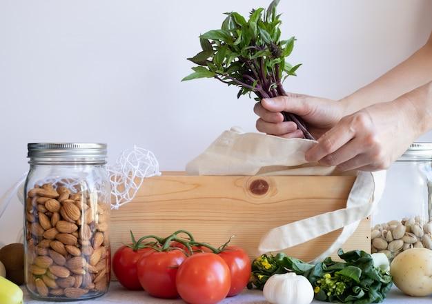 Das frische gemüse von hand in einen baumwollnetzbeutel geben. null abfall lebensstil mit nachhaltigem glas auf weißem hintergrund. kunststofffrei für den einkauf und die lieferung von lebensmitteln. essen und gesunde ernährung.