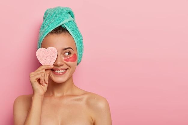 Das fröhliche junge weibliche model hat ein angenehmes lächeln, bedeckt das auge mit einem kosmetischen schwamm, genießt alle vorteile von flecken, reduziert falten, trägt ein gewickeltes handtuch auf dem kopf und hat nach dem aufwachen hautpflege