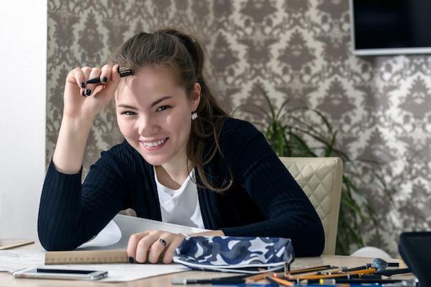 Das frontale porträt einer jungen studentin, die sich am tisch engagiert, zeichnet skizzen