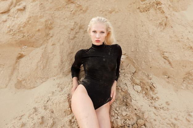 Das frontalporträt einer schönen jungen blonden frau im schwarzen body liegt auf dem sandboden.