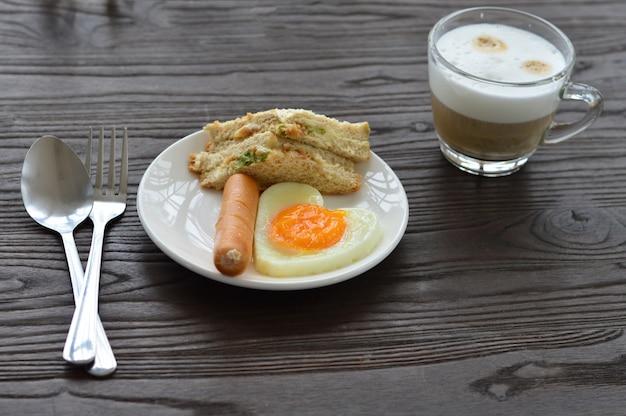 Das frühstück auf dem tisch besteht aus spiegeleiern, würstchen, sandwiches und kaffee.