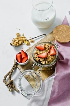 Das frühstück besteht aus bio-müsli, erdbeeren und joghurt.