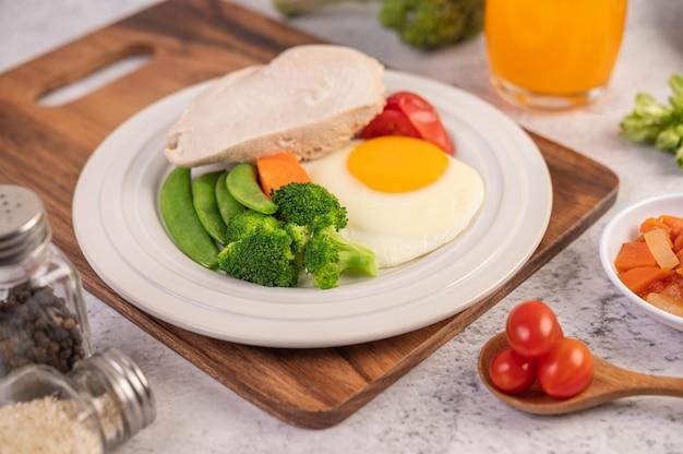 Das frühstück besteht aus hühnchen, spiegeleiern, brokkoli, karotten, tomaten und salat auf einem weißen teller.