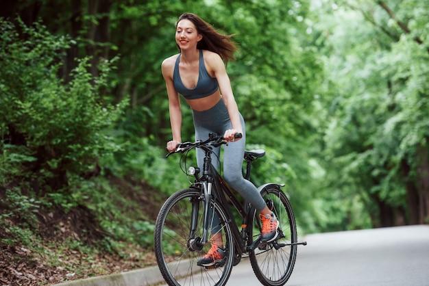 Das fühlt sich großartig an. weiblicher radfahrer auf einem fahrrad auf asphaltstraße im wald am tag