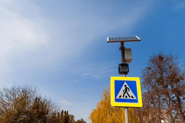 Das fußgängerüberwegschild wird von oben installierten sonnenkollektoren angetrieben