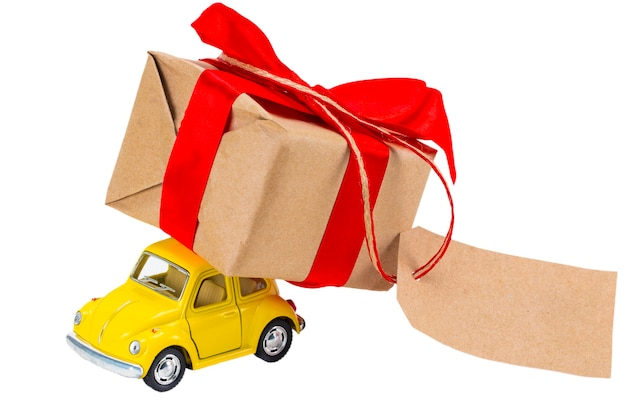 Das gelbe retro-spielzeugauto, das geschenkbox mit etikett mit leerem platz für einen text auf weißem hintergrund liefert.