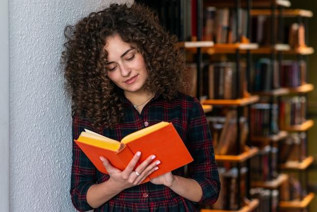 Das gelockte brunettemädchen, das ein buch in ihrer hand hält, lehnte sich an der wand und am ablesen. mädchen steht in der bibliothek