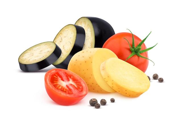 Das gemüse, das auf weißem hintergrund lokalisiert wurde, schnitt tomate, aubergine und kartoffel mit gewürzen