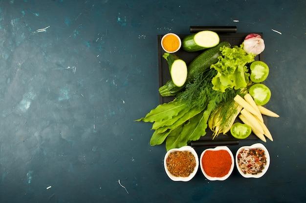 Das gemüse im kasten auf dem stein ein dunkel. junge grüne zwiebel knoblauch zucchini helle gewürze lagern in einem holztablett mit griffen auf einem dunkelen beschaffenen.