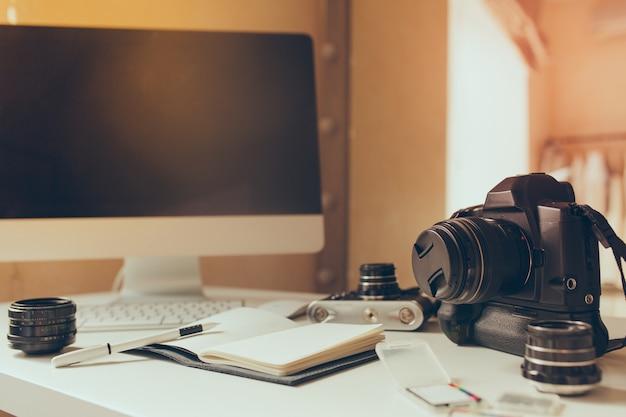 Das geöffnete notizbuch mit leeren seiten liegt mit dem stift neben der tastatur auf dem tisch. innenfoto des arbeitsplatzes mit computer und kamera auf unscharfem hintergrund.