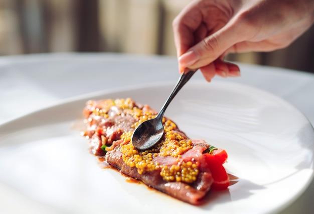 Das gericht ist carpaccio. chefkot mist körniges senfgericht, carpaccio.