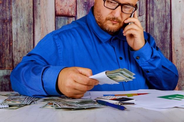Das geschäft, das bargeld wir dollar oben in den händen zählt, bemannen mobiltelefon auf geld