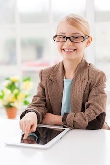 Das geschäft einfacher machen. fröhliches kleines mädchen in brille und formeller kleidung, das am tisch sitzt und an einem digitalen tablet arbeitet