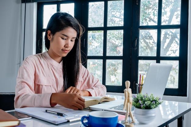 Das geschäftsfrausitzen genießt lesebuch im büro.