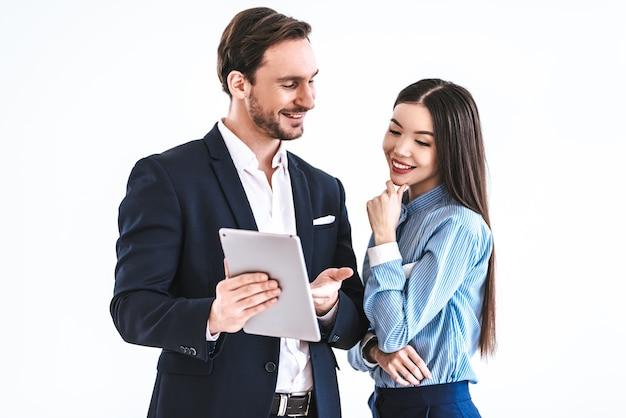Das geschäftspaar mit einer tablette, die auf dem weißen hintergrund steht