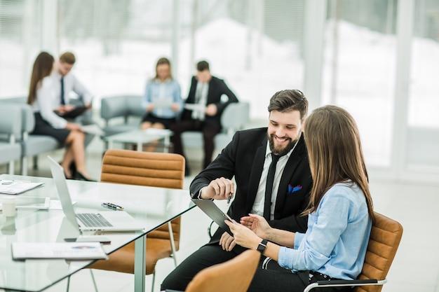 Das geschäftsteam analysiert marketingberichte am arbeitsplatz in einem hellen büro