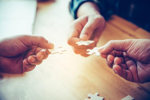 Das geschäftsteam bearbeitet ein stück weiße puzzles, die gleich fallen, um ein vollständiges arbeitsblatt zu erhalten - ein versuch, erfolgreich zu sein.