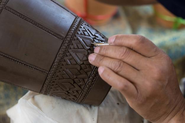 Das geschnitzte keramikglas ist eine traditionelle thailändische handarbeit. es ist eine kunst auf steingut.