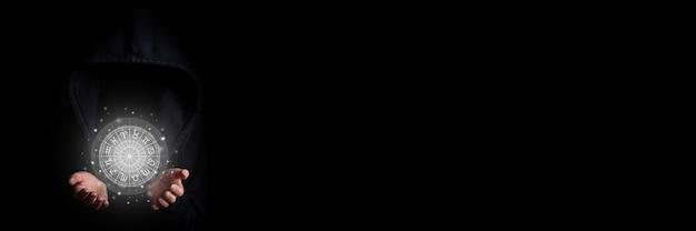 Das gesicht der jungen frau ist in einer schwarzen kapuze nicht sichtbar, die mit handflächen einen leuchtenden tierkreis auf schwarzem hintergrund hält. banner.