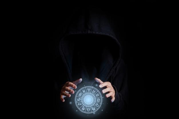 Das gesicht der jungen frau ist in einer schwarzen kapuze nicht sichtbar, die mit handflächen einen leuchtenden tierkreis auf schwarzem hintergrund hält.