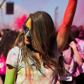 Das gesicht der jungen frauen bedeckt mit holi farbtanzen