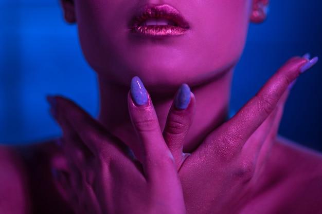 Das gesicht des mädchenmodells auf einem blauen hintergrund mit hellen lippen hält hände um das gesicht.