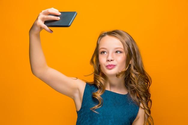 Das gesicht des verspielten glücklichen jugendlich mädchens mit telefon