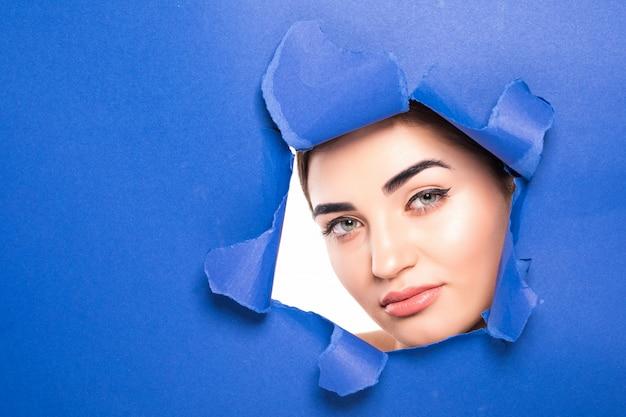 Das gesicht einer jungen schönen frau mit einem hellen make-up und geschwollenen blauen lippen späht in ein loch in blauem papier.