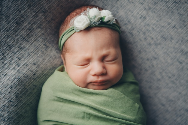 Das gesicht eines kindes mit einem verband mit blumen auf seiner kopfnahaufnahme