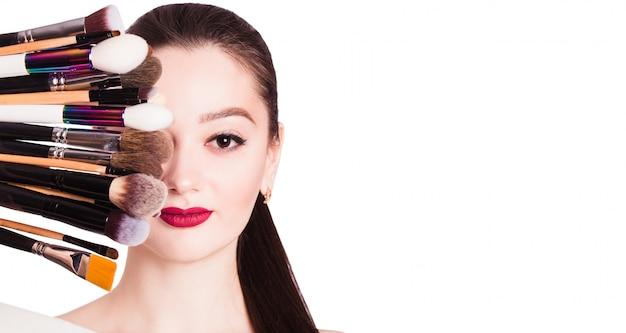 Das gesicht eines schönen mädchens und make-up pinsel auf weißer wand