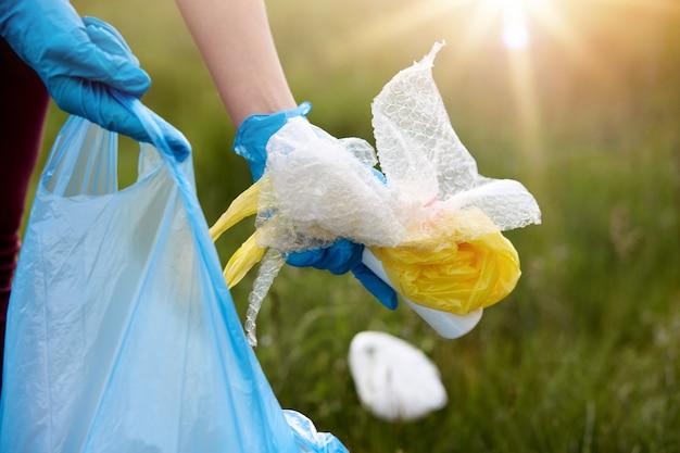 Das gesichtslose porträt einer person, die müll aufnimmt, einen latexblauen einweghandschuh trägt, müll in den händen hält und das feld reinigt, kümmert sich um die ökologie des planeten.