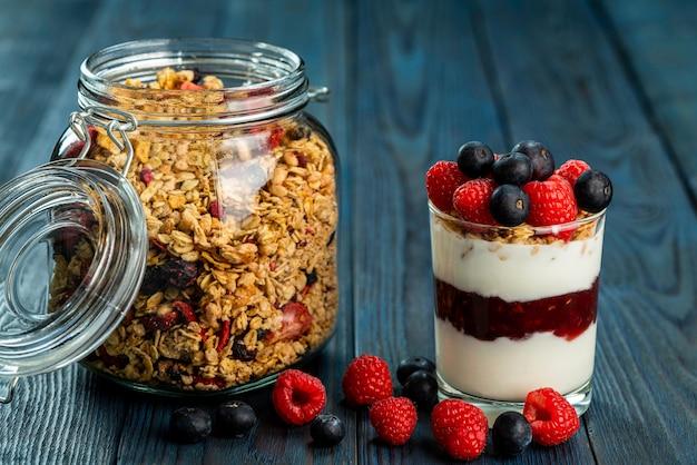 Das gesunde frühstück von joghurt mit müsli, müsli himbeermarmelade und frischen früchten himbeere und heidelbeere