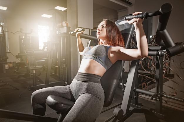 Das gewichtheben der fitnessfrau im fitnessstudio