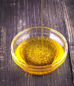 Das gießende speiseöl eine kleine glasschale auf altem holztisch