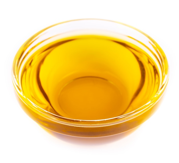 Das gießende speiseöl ist eine kleine glasschale, die auf weiß isoliert ist