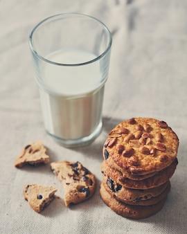 Das glas milch mit einem stapel kekse mit schokoladenstücken und erdnuss auf einem textilhandtuch