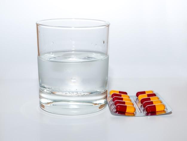 Das glas wasser und medizin kapsel