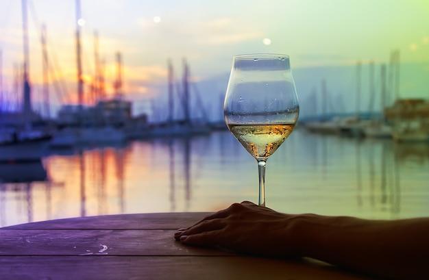 Das glas weißwein vor dem hintergrund eines sonnenuntergangs im hafen mit yachten