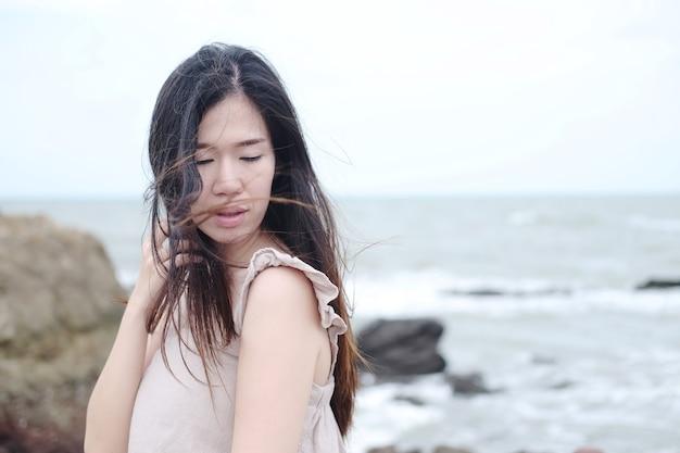 Das glück der asiatischen frau steht auf der holzbrücke, die sich im urlaub ins meer erstreckt