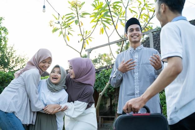 Das glück muslimischer familien, die sich beim treffen die hände schütteln und sich mit familienmitgliedern treffen